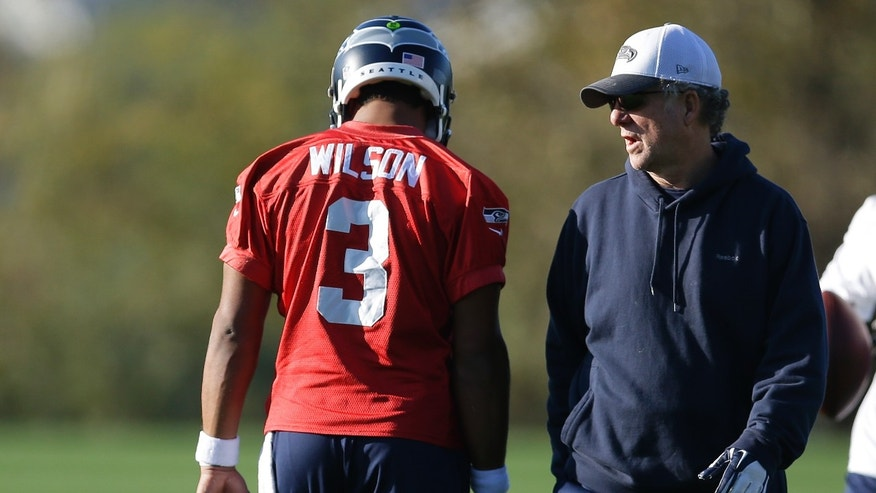 Seattle Seahawks quarterback Russell Wilson (3) talks with quarterbacks coach Carl Smith, right, at the start of NFL football practice, Tuesday, Oct. 22, 2013, in Renton, Wash. (AP Photo/Ted S. Warren)