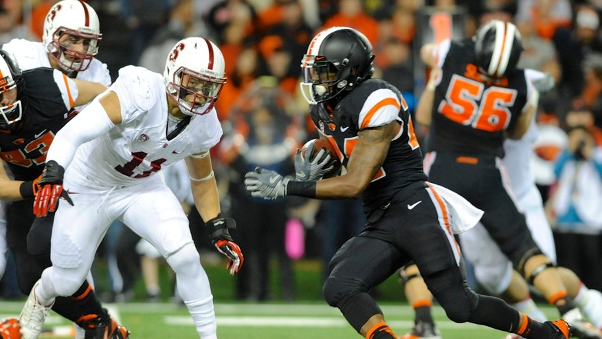 Oregon State's Storm Woods (24) runs against Stanford's Shayne Skov (11) during the first half of an NCAA college football game in Corvallis, Ore., Saturday Oct. 26, 2013. (AP Photo/Greg Wahl-Stephens)