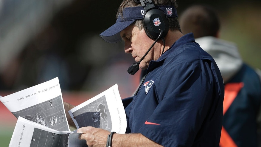 New England Patriots head coach Bill Belichick studies pictures on the sideline in the second quarter of an NFL football game against the Miami Dolphins Sunday, Oct. 27, 2013, in Foxborough, Mass. (AP Photo/Steven Senne)