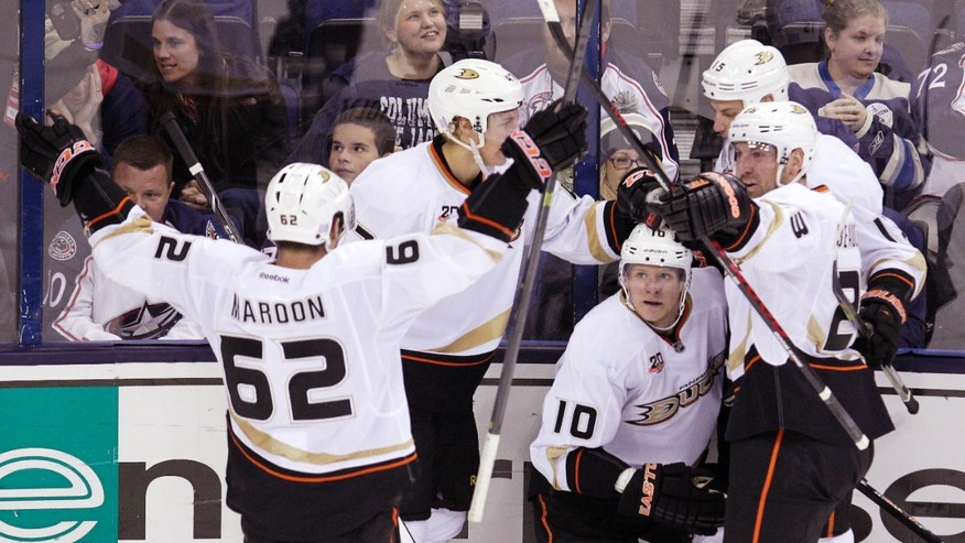 Anaheim Ducks' Corey Perry, kneeling, and teammates celebrate Perry's game-winning goal against the Columbus Blue Jackets during the third period of an NHL hockey game Sunday, Oct. 27, 2013, in Columbus, Ohio. The Ducks beat the Blue Jackets 4-3. (AP Photo/Jay LaPrete)