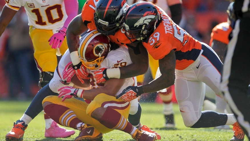 Washington Redskins running back Roy Helu (29) is tackled by Denver Broncos defensive end Robert Ayers (91) and outside linebacker Danny Trevathan (59) in the second quarter of an NFL football game, Sunday, Oct. 27, 2013, in Denver. (AP Photo/Joe Mahoney)