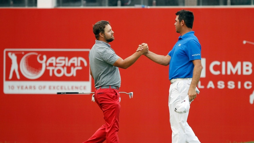 Ryan Moore, left, of the U.S. is congratulated by his compatriot Gary Woodland after winning in a playoff of the CIMB Classic golf tournament at the Kuala Lumpur Golf and Country Club in Kuala Lumpur, Malaysia, Monday, Oct. 28, 2013. (AP Photo/Lai Seng Sin)