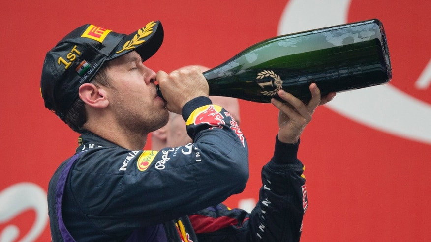 Red Bull driver Sebastian Vettel of Germany -drinks champagne after winning the Indian Formula One Grand Prix and his 4th straight F1 world drivers championship at the Buddh International Circuit in Noida, India, Sunday, Oct. 27, 2013. (AP Photo/Mark Baker)