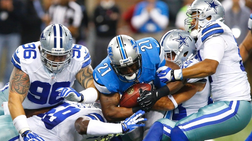 Detroit Lions running back Reggie Bush (21) is stopped by Dallas Cowboys inside linebacker Ernie Sims (59), defensive tackle Nick Hayden (96), defensive back Jeff Heath, second from right, and defensive end Kyle Wilber, right, in the first half of an NFL football game in Detroit, Sunday, Oct. 27, 2013. (AP Photo/Duane Burleson)