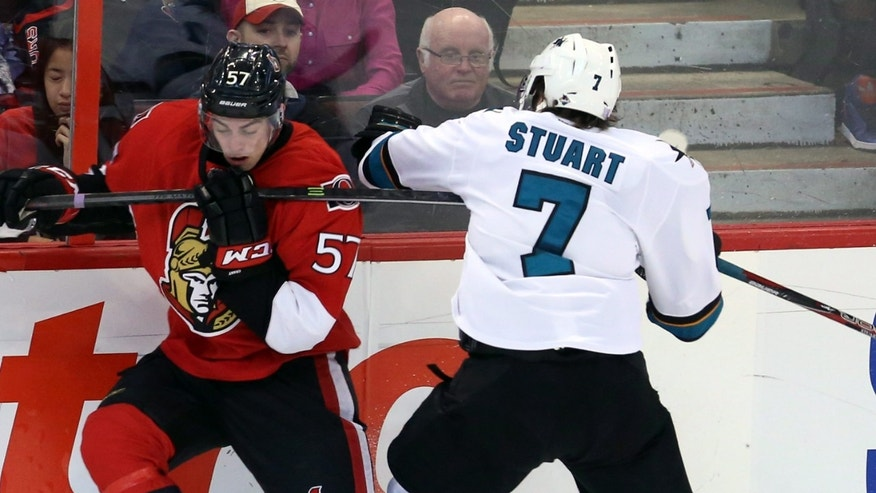 Ottawa Senators' Derek Grant (57) and San Jose Sharks' Brad Stuart battle for a loose puck along the boards during the second period NHL hockey game in Ottawa, Ontario, on Sunday, Oct. 27, 2013. (AP Photo/The Canadian Press, Fred Chartrand)