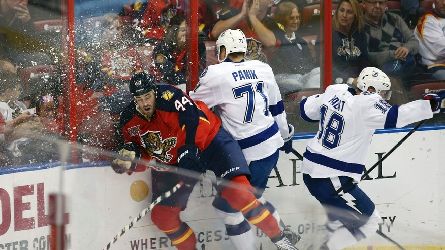 Florida Panthers' Erik Gudbranson (44), along with Tampa Bay Lightning's Richard Panik (77) and Ondrej Palat (18), slams into the glass during the second period of an NHL hockey game in Sunrise, Fla., Sunday, Oct. 27, 2013. (AP Photo/J Pat Carter)