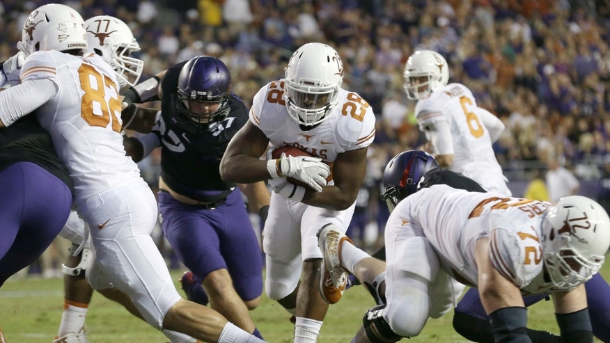Texas running back Malcolm Brown (28) finds a hole and runs in to score a touchdown during the first half of an NCAA college football game against TCU, Saturday, Oct. 26, 2013, in Fort Worth, Texas.  Texas' Geoff Swaim (82) and Mason Walters (72) and TCU's Jon Koontz (97) are in on the play. (AP Photo/LM Otero)