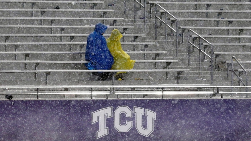 Fans sit in the stands during a thunder delay in the second quarter of an NCAA college football game between Texas and TCU, Saturday, Oct. 26, 2013, in Fort Worth, Texas. (AP Photo/LM Otero)