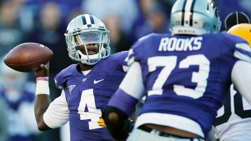 Kansas State quarterback Daniel Sams (4) throws a touchdown during the second half of an NCAA college football game against West Virginia in Manhattan, Kan., Saturday, Oct. 26, 2013. Kansas State won 35-12. (AP Photo/Orlin Wagner)
