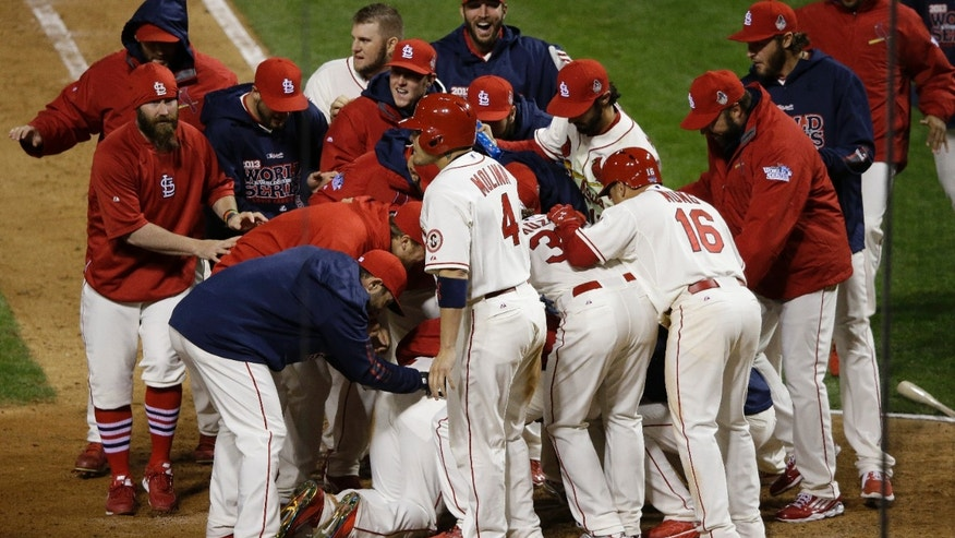 St. Louis Cardinals players celebrate with Allen Craig, on ground, after Craig scored the game-winning run on an obstruction play in ninth inning of Game 3 of baseball's World Series against the Boston Red Sox  Saturday, Oct. 26, 2013, in St. Louis. The Cardinals won 5-4 to take a 2-1 lead in the series. (AP Photo/Charlie Neibergall)