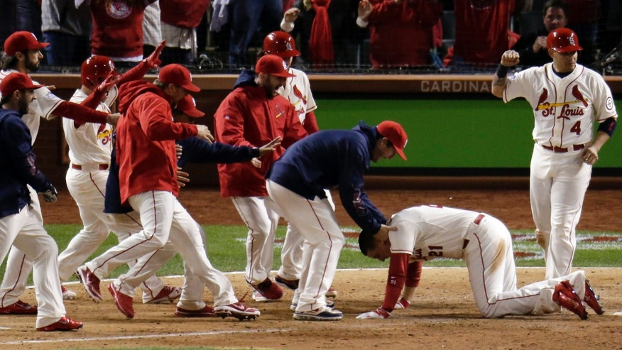 Teammates mob St. Louis Cardinals' Allen Craig at home after Craig scored the game-winning run on an obstruction call during the ninth inning of Game 3 of baseball's World Series against the Boston Red Sox Saturday, Oct. 26, 2013, in St. Louis. (AP Photo/Charlie Riedel)
