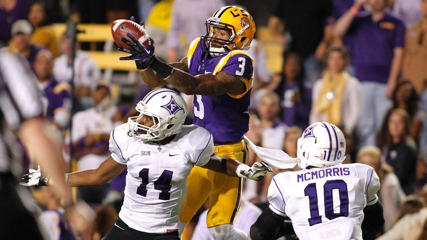 LSU wide receiver Odell Beckham (3) pulls in a reception for a 37-yard touchdown over Furman cornerback Reggie Thomas (14) and safety Marcus McMorris (10) during the second quarter of the NCAA college football game in Baton Rouge, La., Saturday, Oct, 26, 2013. (AP Photo/Jonathan Bachman)