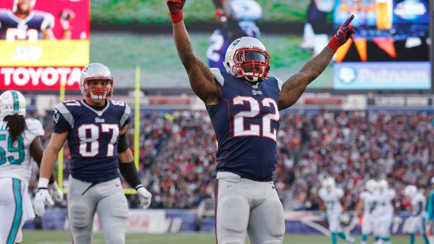 New England Patriots running back Stevan Ridley (22) celebrates his touchdown against the Miami Dolphins in the fourth quarter of an NFL football game Sunday, Oct. 27, 2013, in Foxborough, Mass. At left is Patriots tight end Rob Gronkowski. (AP Photo/Michael Dwyer)
