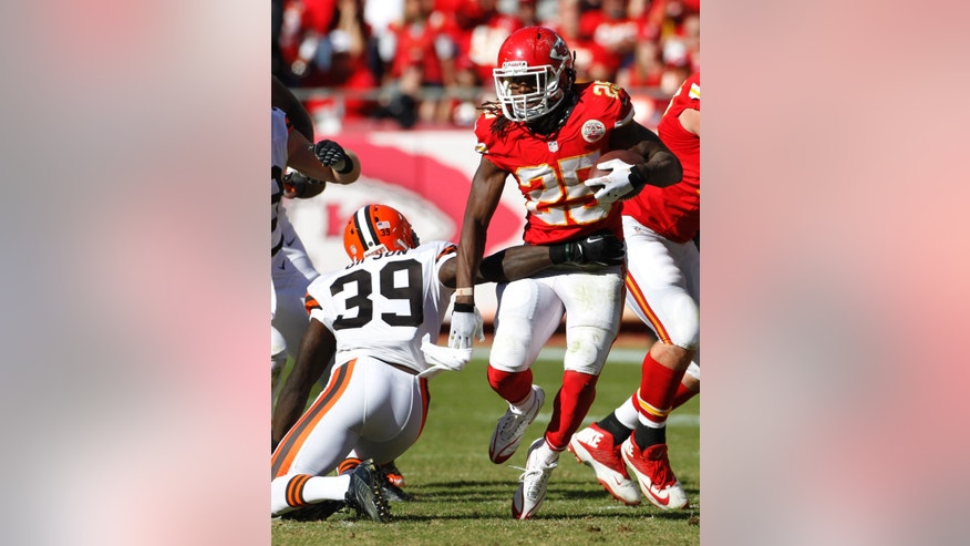 Kansas City Chiefs running back Jamaal Charles (25) breaks a tackle by Cleveland Browns free safety Tashaun Gipson (39) during the second half of an NFL football game in Kansas City, Mo., Sunday, Oct. 27, 2013. The Chiefs defeated the Browns 23-17. (AP Photo/Colin E. Braley)