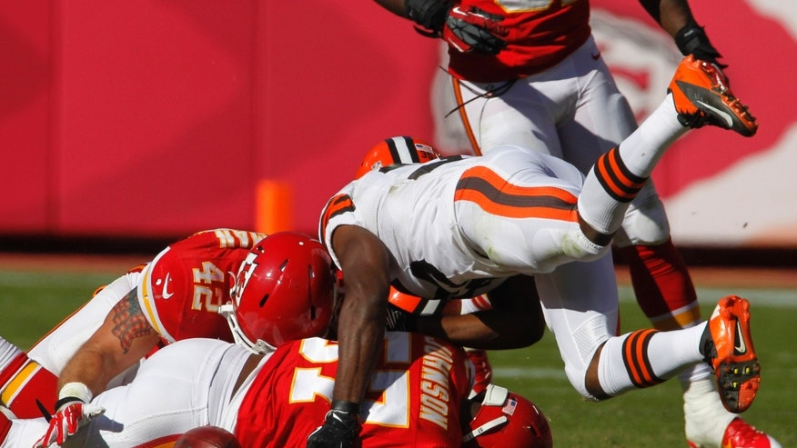 Cleveland Browns running back Fozzy Whittaker (35) dives onto Kansas City Chiefs' Nico Johnson (57) and Anthony Sherman (42) to try and recover a fumble during the second half of an NFL football game in Kansas City, Mo., Sunday, Oct. 27, 2013. Chiefs' Derrick Johnson recovered the ball. The Chiefs defeated the Browns 23-17. (AP Photo/Colin E. Braley)