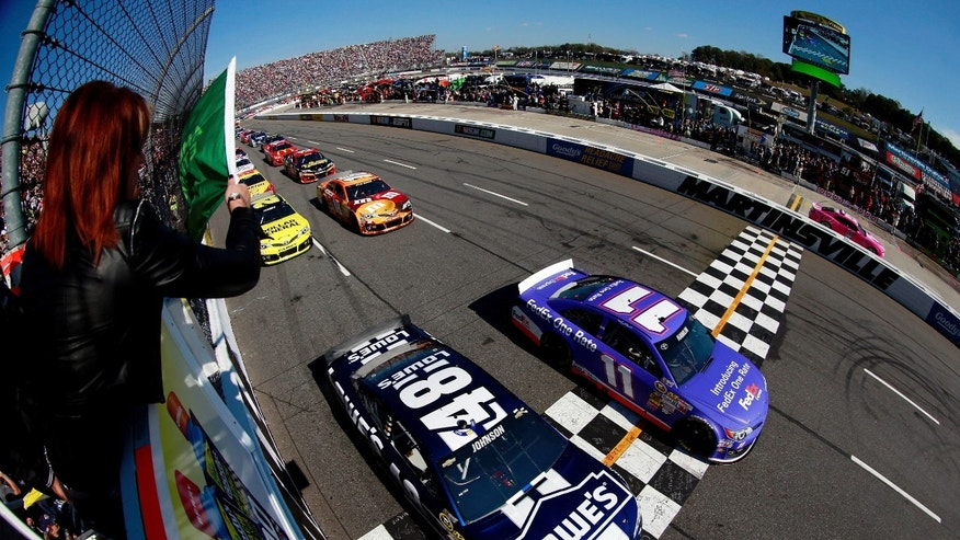 In a photo made with a wide angle lens Denny Hamlin (11) and  Jimmie Johnson (48) lead the field to start the NASCAR Sprint Cup auto race at Martinsville Speedway on Oct. 27, 2013 in Martinsville, Va.  (AP Photo/Chris Trotman, pool)