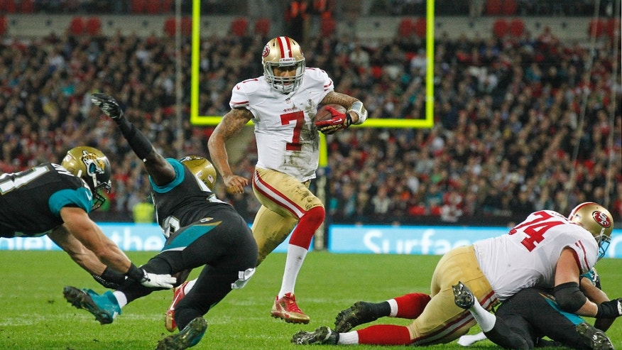 San Francisco 49ers quarterback Colin Kaepernick (7) races through to score a touchdown during the NFL football game between San Francisco 49ers and Jacksonville Jaguars at Wembley Stadium in London, Sunday, Oct. 27, 2013. (AP Photo/Sang Tan)