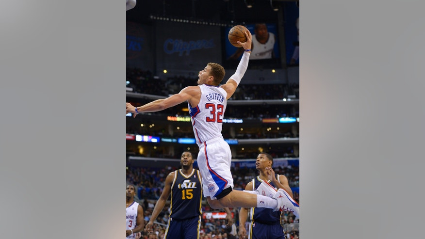 Los Angeles Clippers power forward Blake Griffin, center, goes up for a dunk as Utah Jazz power forward Derrick Favors and point guard Scott Machado look on during the first half of their NBA basketball game, Wednesday, Oct. 23, 2013, in Los Angeles. (AP Photo/Mark J. Terrill)