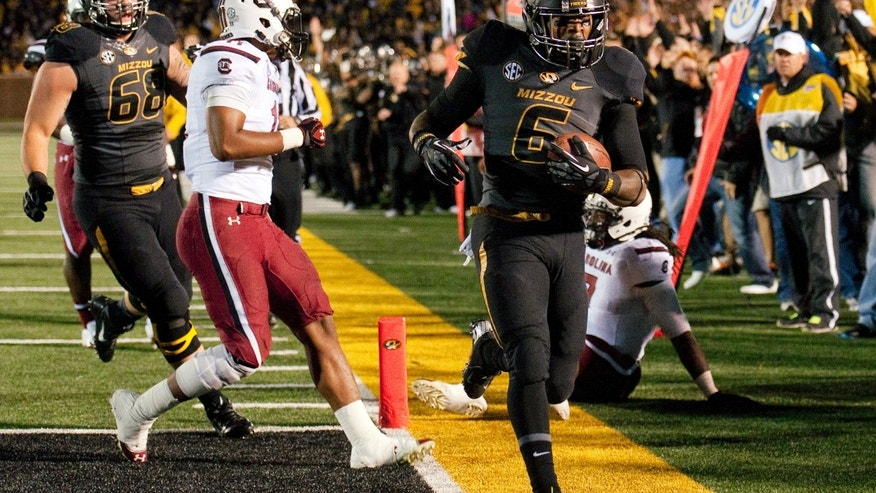 Missouri's Marcus Murphy, right, scores a touchdown in front of South Carolina's T.J. Holloman, center, and Missouri's Justin Britt (68) during the first quarter of an NCAA college football game Saturday, Oct. 26, 2013, in Columbia, Mo. (AP Photo/L.G. Patterson)