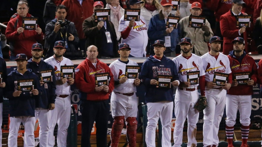 St. Louis Cardinals players and coaches hold up answer to cancer signs after the fifth inning of Game 4 of baseball's World Series between the Boston Red Sox and the St. Louis Cardinals Sunday, Oct. 27, 2013, in St. Louis. (AP Photo/Charlie Riedel)