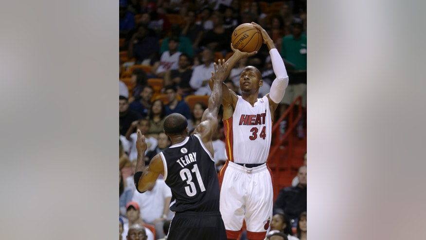 Miami Heat shooting guard Ray Allen (34) shoots for a three-pointer against Brooklyn Nets shooting guard Jason Terry (31) in the second period of an NBA preseason basketball game, Friday, Oct. 25, 2013, in Miami. (AP Photo/Alan Diaz)
