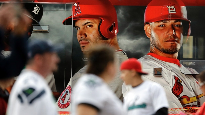 Fans walk past photos of former St. Louis Cardinals Albert Pujols, left, and catcher Yadier Molina before Game 5 of baseball's World Series against the Boston Red Sox Monday, Oct. 28, 2013, in St. Louis. (AP Photo/Jeff Roberson)