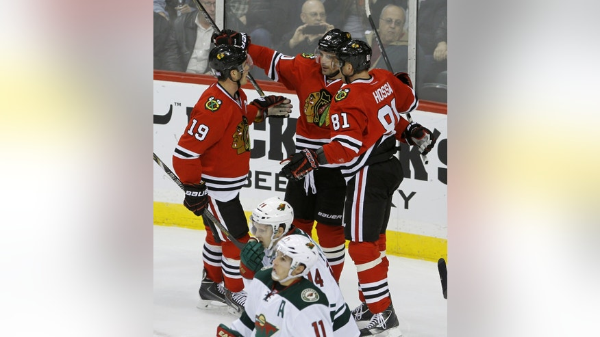 Chicago Blackhawks center Jonathan Toews (19) and right wing Marian Hossa (81) of the Czech Republic congratulate center Patrick Sharp  after his goal on Minnesota Wild goalie Niklas Backstrom during the first period of an NHL hockey game in St. Paul , Minn., Monday, Oct. 28, 2013. (AP Photo/Ann Heisenfelt)