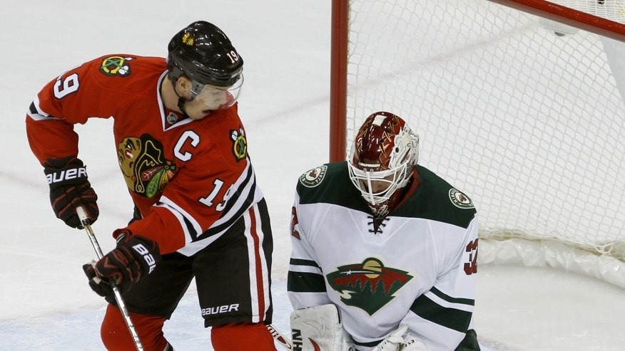 Chicago Blackhawks center Jonathan Toews (19) watches as Minnesota Wild goalie Niklas Backstrom (32) of Finland stops a shot during the first period of an NHL hockey game in St. Paul , Minn., Monday, Oct. 28, 2013. (AP Photo/Ann Heisenfelt)