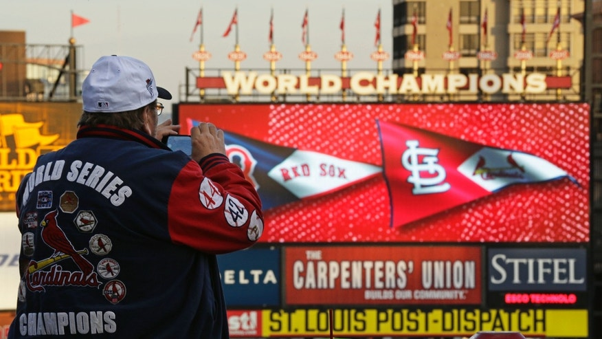 John Koenig takes a photo as players warm up for Game 5 of baseball's World Series between the Boston Red Sox and the St. Louis Cardinals Monday, Oct. 28, 2013, in St. Louis. (AP Photo/Charlie Riedel)