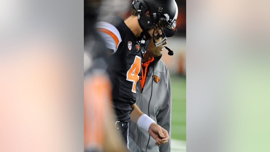 Oregon State's head coach Mike Riley speaks with quarterback Sean Mannion (4) on the sideline during the second half of an NCAA college football game against Stanford in Corvallis, Ore., Saturday Oct. 26, 2013. Stanford beat Oregon State 20-12. (AP Photo/Greg Wahl-Stephens)