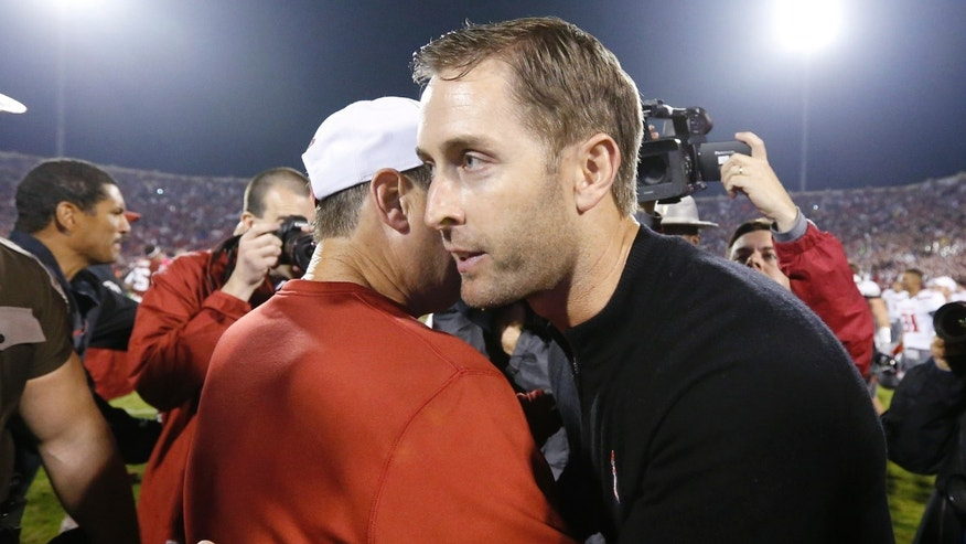 Oklahoma head coach Bob Stoops, left, and Texas Tech head coach Kliff Kingsbury, right, meet at midfield following their NCAA college football game in Norman, Okla., Saturday, Oct. 26, 2013. Oklahoma won 38-30. (AP Photo/Sue Ogrocki)