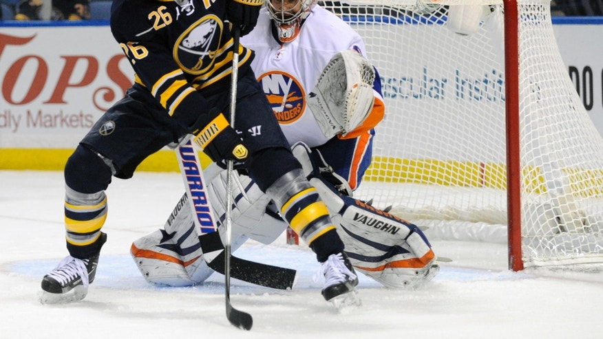 File- This Feb. 23, 2013 file photo shows Buffalo Sabres' left winger Thomas Vanek (26), of Austria, getting ready to deflect the puck in front of New York Islanders' goaltender Evgeni Nabokov (20), of Russia, during the first period of an NHL hockey game in Buffalo, N.Y., The New York Islanders announced Sunday Oct. 27, 2013, that they have acquired Vanek from the Buffalo Sabres in exchange for Matt Moulson, a first round selection in the 2014 NHL draft and a second round selection in 2015. (AP Photo/Gary Wiepert, File)