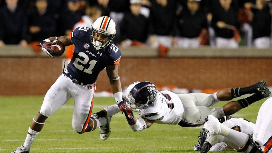 Auburn running back Tre Mason (21) gets around the corner for a first down as Florida Atlantic defensive back Christian Milstead tries to tackle him during the first half of an NCAA college football game on Saturday, Oct. 26, 2013, in Auburn, Ala. (AP Photo/Butch Dill)