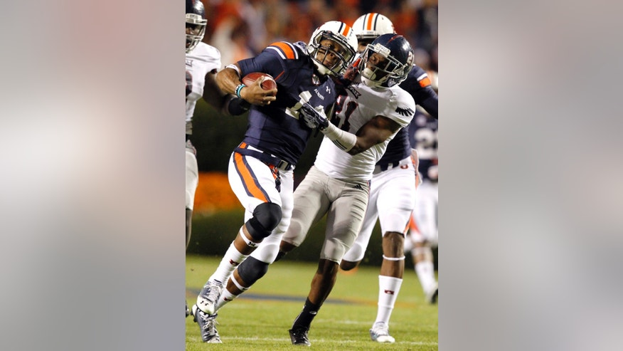 Auburn quarterback Nick Marshall, left, stiff arms Florida Atlantic defensive back D'Joun Smith as he carried the ball for first down during the first half of an NCAA college football game on Saturday, Oct. 26, 2013, in Auburn, Ala. (AP Photo/Butch Dill)