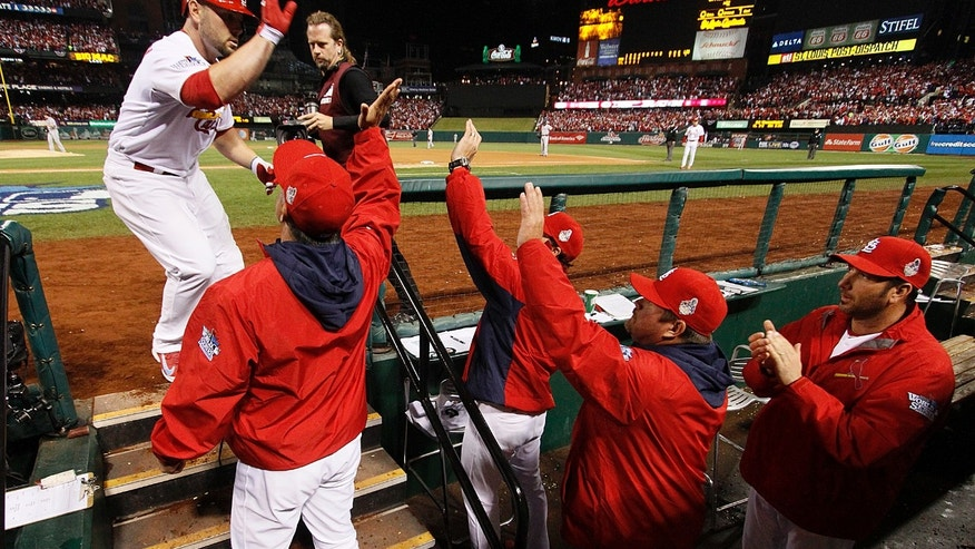 St. Louis Cardinals' Matt Holliday (left) is congratuled by coaches, including (from left) Mike Aldrete, Mike Matheny, Derek Lilliquist and John Mabry after hitting a solo home run in the fourth inning during Game 5 of the World Series between the St. Louis Cardinals and the Boston Red Sox on Monday, Oct. 28, 2013, at Busch Stadium in St. Louis.  (AP Photo/St. Louis Post-Dispatch, Chris Lee)