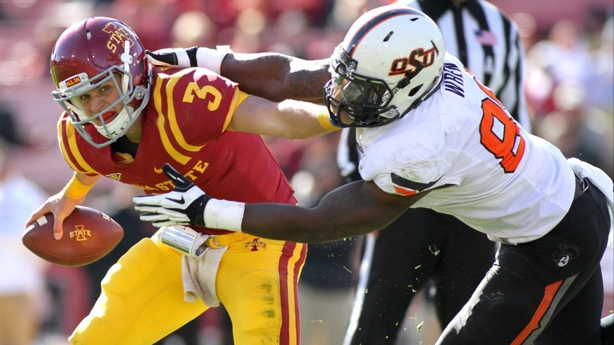 Oklahoma State defensive end Sam Wrend (89) grabs Iowa State quarterback Grant Rohach (3) for a sack during the second half of an NCAA college football game in Ames, Iowa, Saturday, Oct. 26, 2013. Oklahoma State won 58-27. (AP Photo by Justin Hayworth)