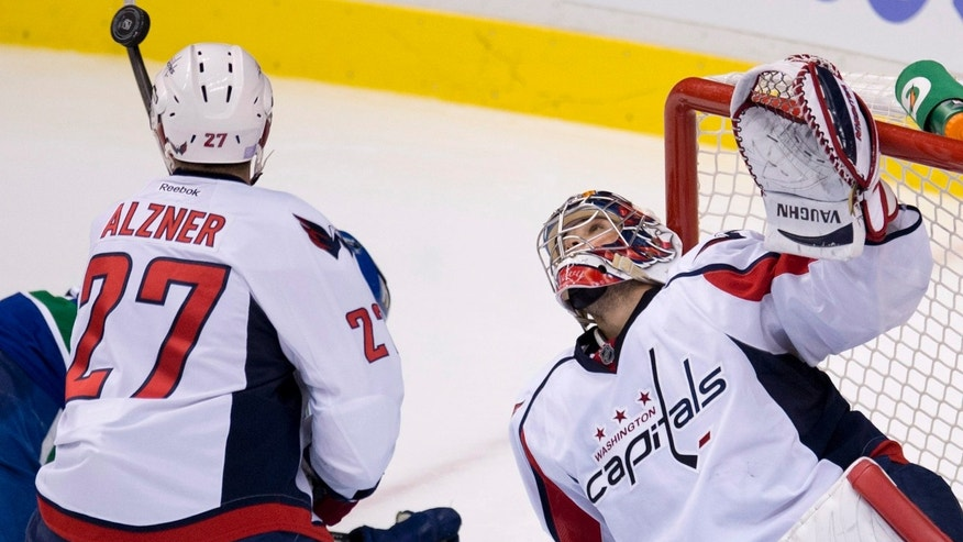 Washington Capitals defenceman Karl Alzner (27) and Capitals goalie Michal Neuvirth (30) stop a shot from the Vancouver Canucks during the second period of NHL hockey action in Vancouver, British Columbia on Monday, Oct. 28, 2013. (AP Photo/The Canadian Press, Jonathan Hayward)