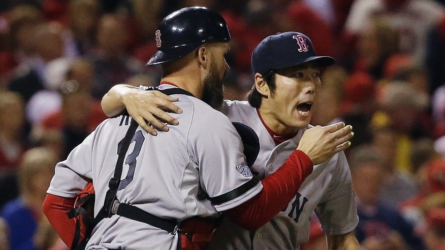 Boston Red Sox relief pitcher Koji Uehara hugs catcher David Ross after getting St. Louis Cardinals' Matt Holliday to fly out and end Game 5 of baseball's World Series Monday, Oct. 28, 2013, in St. Louis. The Red Sox won 3-1 to take a 3-2 lead in the series. (AP Photo/Jeff Roberson)