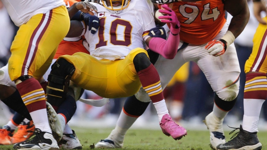 Washington Redskins quarterback Robert Griffin III (10) looks for the ball he fumbled while being sacked by the Denver Broncos in the fourth quarter of an NFL football game, Sunday, Oct. 27, 2013, in Denver. (AP Photo/Joe Mahoney)