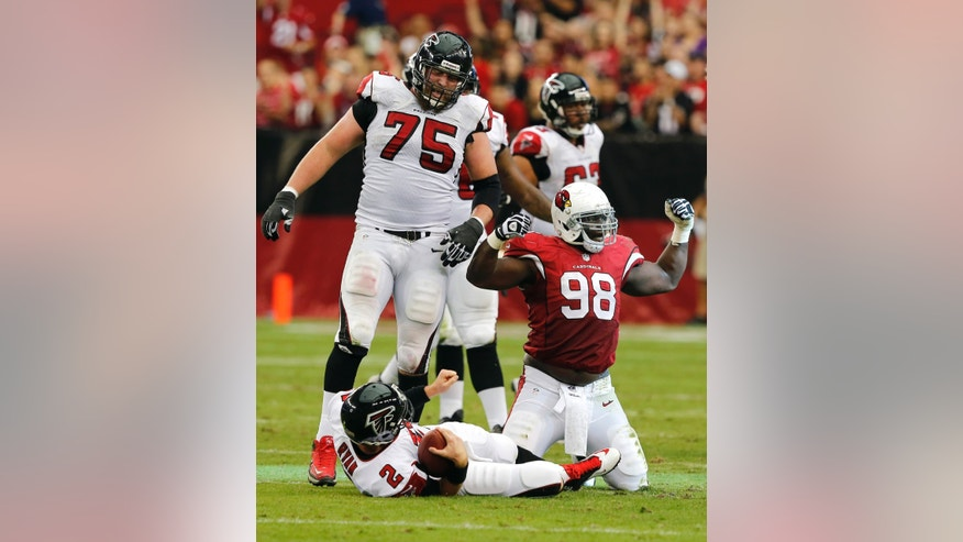 Arizona Cardinals defensive end Frostee Rucker (98) celebrates his sack of Atlanta Falcons quarterback Matt Ryan (2) for a 10-yard loss as Atlanta Falcons guard Garrett Reynolds (75) watches during the second half of an NFL football game Sunday, Oct. 27, 2013, in Glendale, Ariz. (AP Photo/Rick Scuteri)