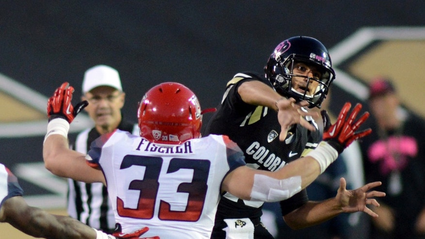 Colorado quarterback Sefo Liufau throws with pressure from Arizona's Jake Fischer during an NCAA college football game on Saturday, Oct. 26, 2013, in Boulder, Colo. (AP Photo/The Daily Camera, Cliff Grassmick)