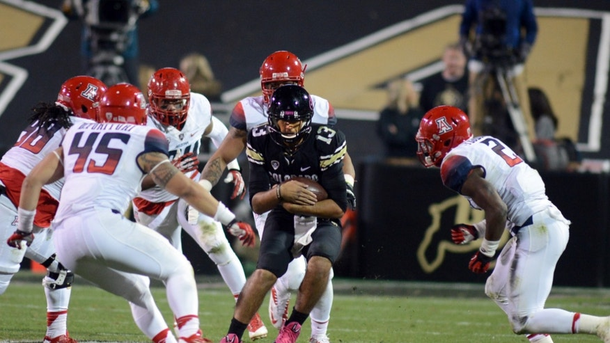 Colorado quarterback, Sefo Liufau, is surrounded by Arizona defenders late in the game on October 26, 2013 game in Boulder, Colorado. (AP Photo/The Daily Camera, Cliff Grassmick)