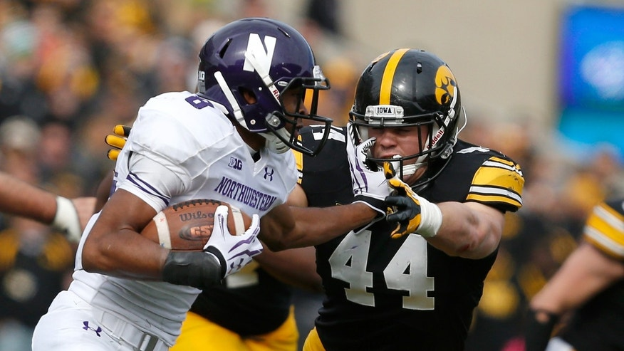Northwestern running back Stephen Buckley (8) is wrapped up by Iowa Hawkeyes linebacker James Morris (44) during the first half of an NCAA college football game Saturday, Oct. 26, 2013, in Iowa City, Iowa.  (AP Photo/Brian Ray)