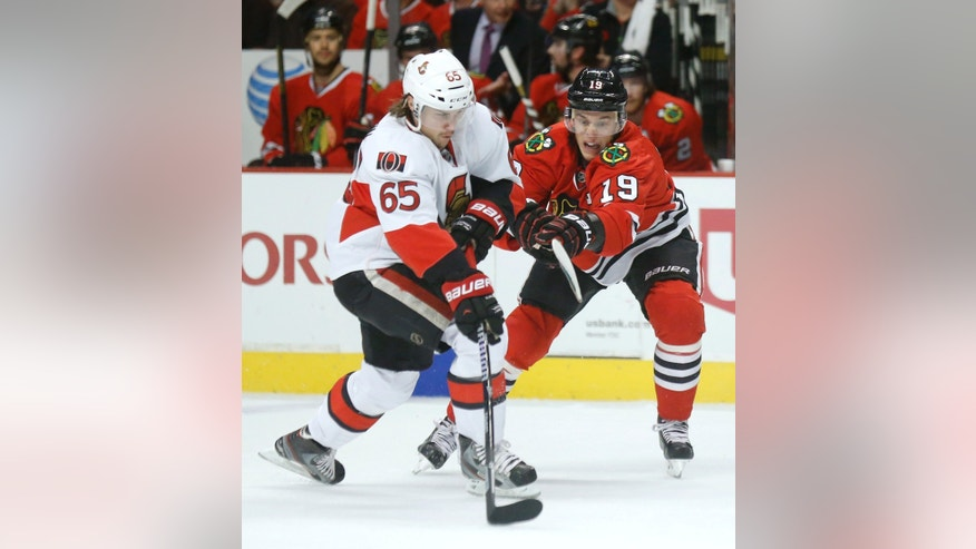 Ottawa Senators defenseman Erik Karlsson (65) passes the puck past Chicago Blackhawks center Jonathan Toews (19) during the first period of an NHL hockey game Tuesday, Oct. 29, 2013, in Chicago. (AP Photo/Charles Rex Arbogast)
