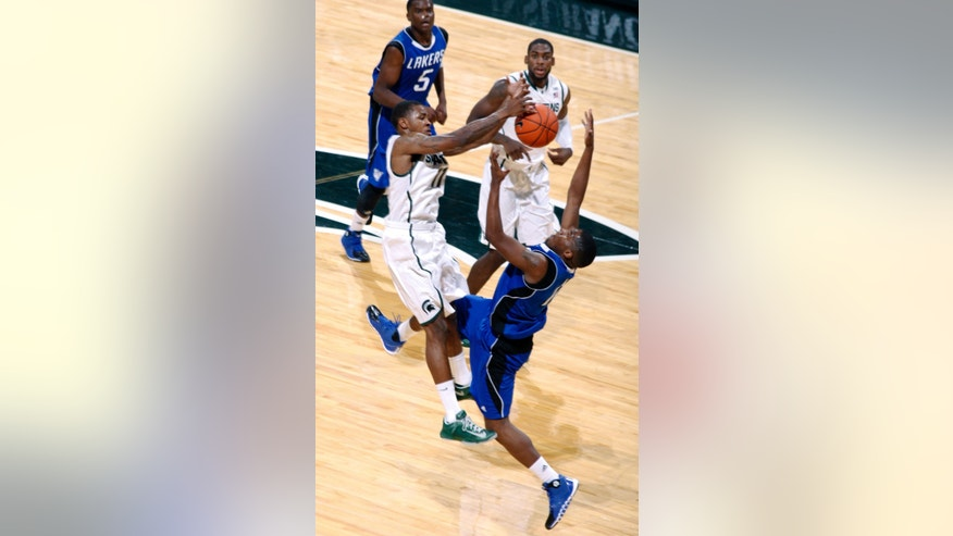 Michigan State's Keith Appling, left, and Grand Valley State's Rob Woodson leap to catch a high ball during the first half of an NCAA college basketball exhibition game, Tuesday, Oct. 29, 2013, in East Lansing, Mich. Watching at rear are Grand Valley State's Trevin Alexander (5) and Michigan State's Branden Dawson. (AP Photo/Al Goldis)