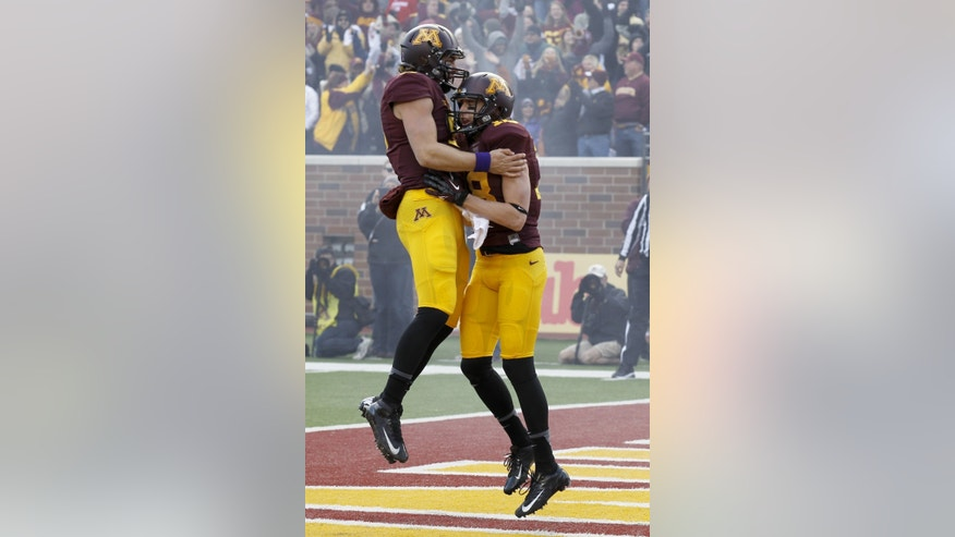 Minnesota quarterback Philip Nelson, left, and wide receiver Derrick Engel, right, celebrate Engel's touchdown during the second quarter of an NCAA college football game against Nebraska in Minneapolis, Saturday, Oct. 26, 2013. (AP Photo/Ann Heisenfelt)