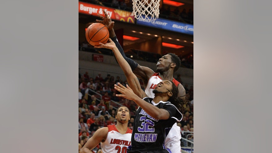 Louisville's Montrezl Harrell, rear, attempts to block the shot of Kentucky Wesleyan's Donovan Johnson during the first half of an exhibition NCAA college basketball game Tuesday, Oct. 29, 2013, in Louisville, Ky. (AP Photo/Timothy D. Easley)