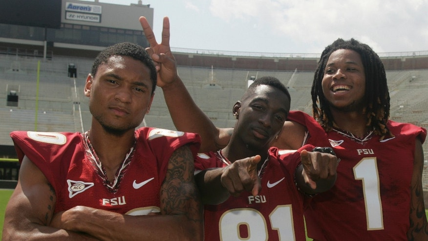 FILE - In this Aug. 12, 2012 file photo, Florida State wide receivers Rashad Greene (80), Kenny Shaw (81) and Kelvin Benjamin (1) have fun during a photo shoot during the Seminoles' football media day in Tallahassee, Fla. No. 3-ranked Florida State has a Heisman Trophy candidate in Jameis Winston, but his receivers corps makes life much easier as one of the top corps in the nation. No. 7 Miami must control the trio of  Greene, Shaw and Benjamin to have a chance at an upset. (AP Photo/Phil Sears, File)