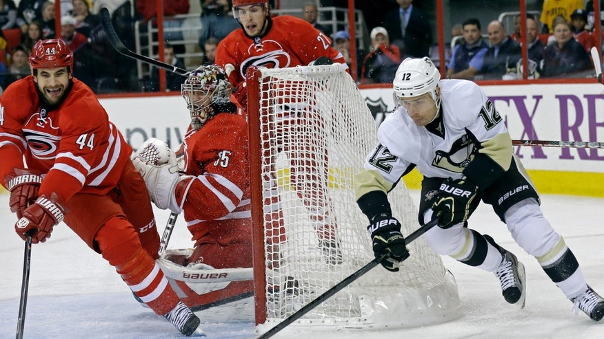 Pittsburgh Penguins' Chuck Kobasew (12) and Carolina Hurricanes' Jay Harrison (44) reach for the puck as Hurricanes goalie Justin Peters (35) defends the goal during the first period of an NHL hockey game in Raleigh, N.C., Monday, Oct. 28, 2013. (AP Photo/Gerry Broome)