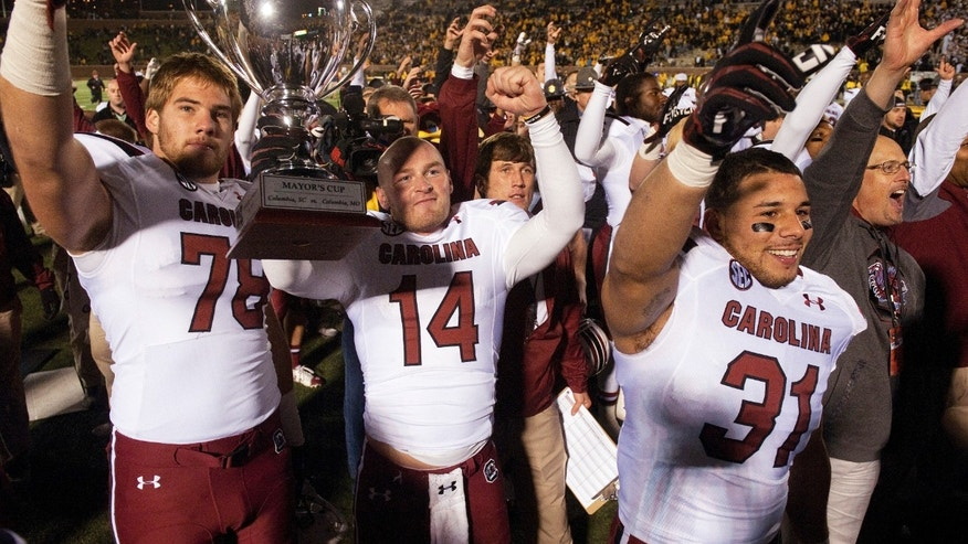 South Carolina's Connor Shaw, center, holds the Mayors Cup as he celebrates with teammates Cody Gibson, left, and Jordan Diaz, right, after the team defeated Missouri 27-24 in an NCAA college football game Saturday, Oct. 26, 2013, in Columbia, Mo. (AP Photo/L.G. Patterson)